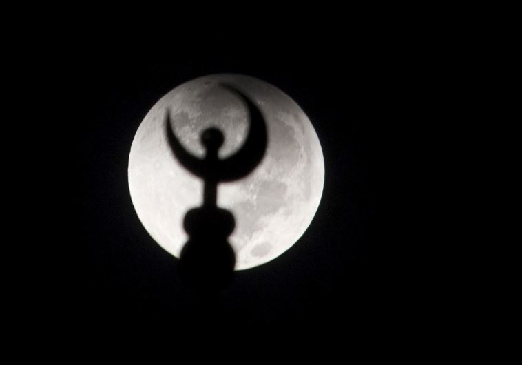 "A minaret of a mosque is silhouetted against the moon at the start of a ""supermoon"" lunar eclipse"
