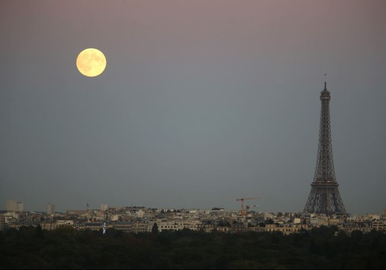 A super moon rises in the sky near the Eiffel tower as seen from Suresnes, Western Paris