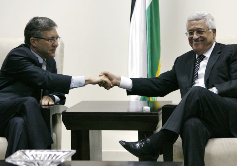 Palestinian Authority President Mahmoud Abbas (R) shakes hands with ex-justice minister Yossi Beilin