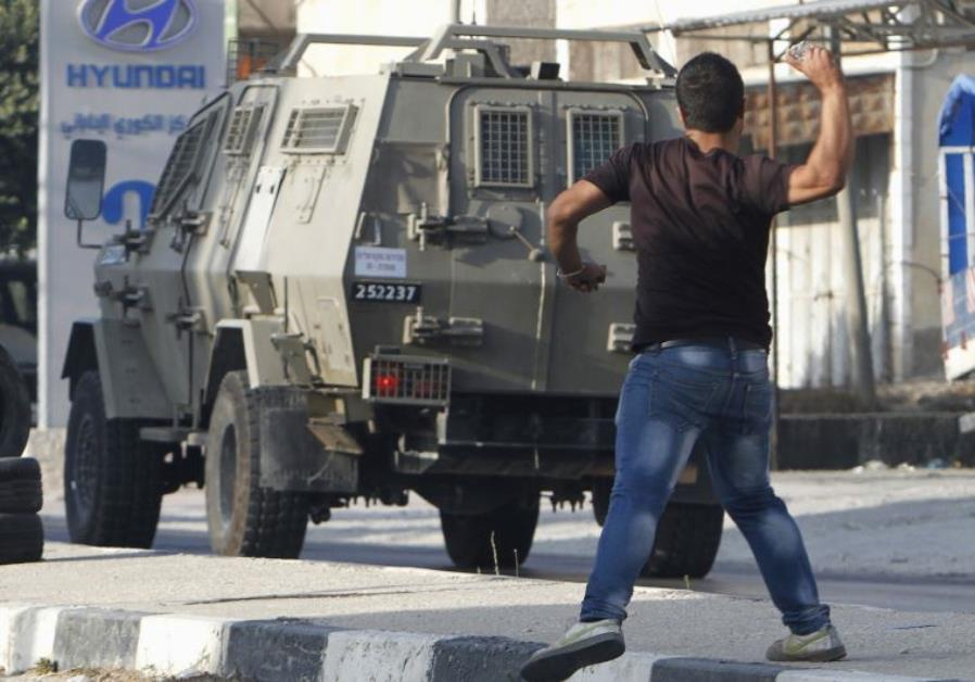 A Palestinian youth hurls stones at Israeli troops during clashes in Nablus