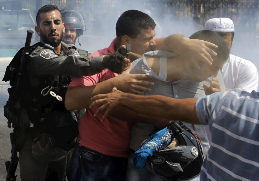 A Border Policeman uses pepper spray on a Palestinian man during clashes in east Jerusalem