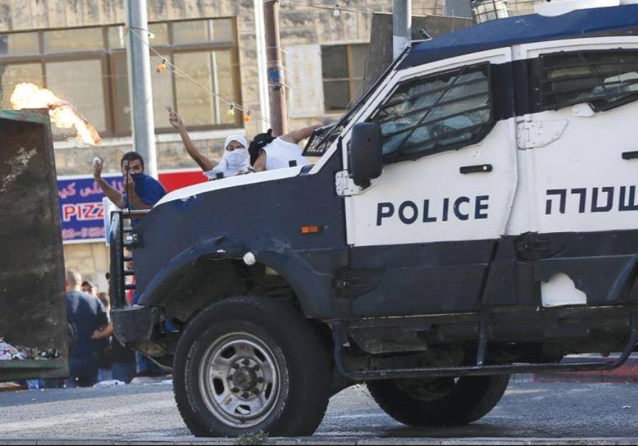 A POLICE vehicle is targeted by Arab rioters.