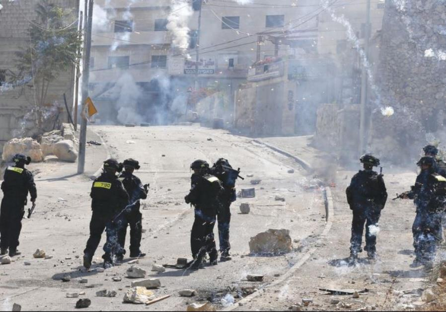 FIREWORKS FALL near policemen during clashes in the capital's Isawiya neighborhood