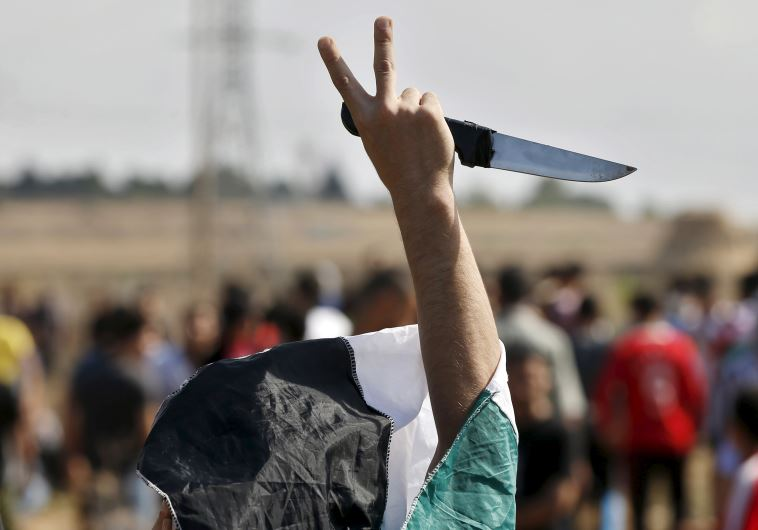 A masked Palestinian protester holds a knife during a protest in Gaza