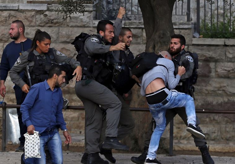 Border Police officers scuffle with a Palestinian protester as they detain him near Damascus Gate