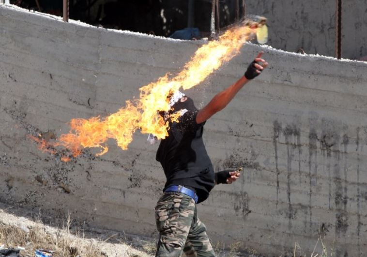 A Palestinian protester throws a Molotov cocktail towards Israeli security forces