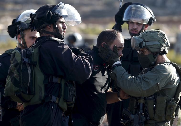 Israeli policemen detain a Palestinian protester during clashes near the Jewish settlement of Beit E