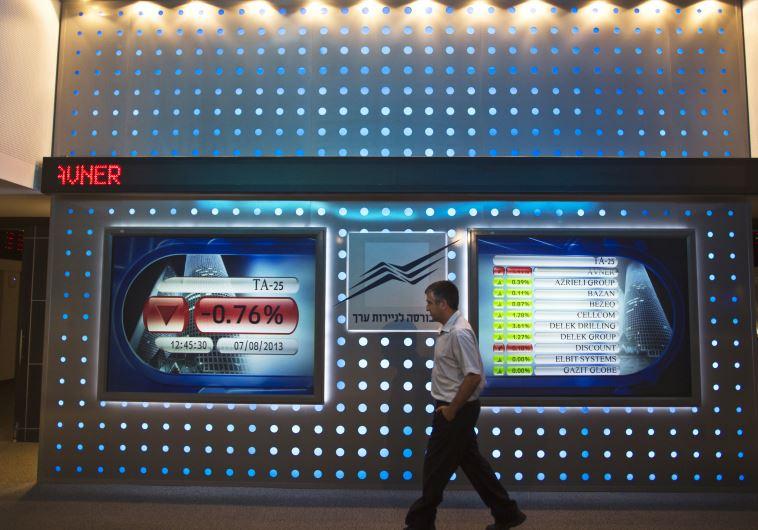 An employee walks past a screen displaying market data at the Tel Aviv Stock Exchange