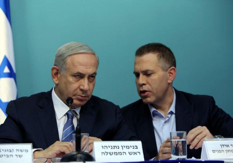 Prime Minister Benjamin Netanyahu listens to Public Security Minister Gilad Erdan (R)