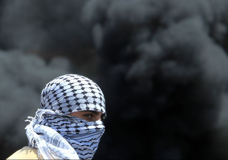A masked Palestinian protester looks on amid the smoke of burning tires during clashes with IDF