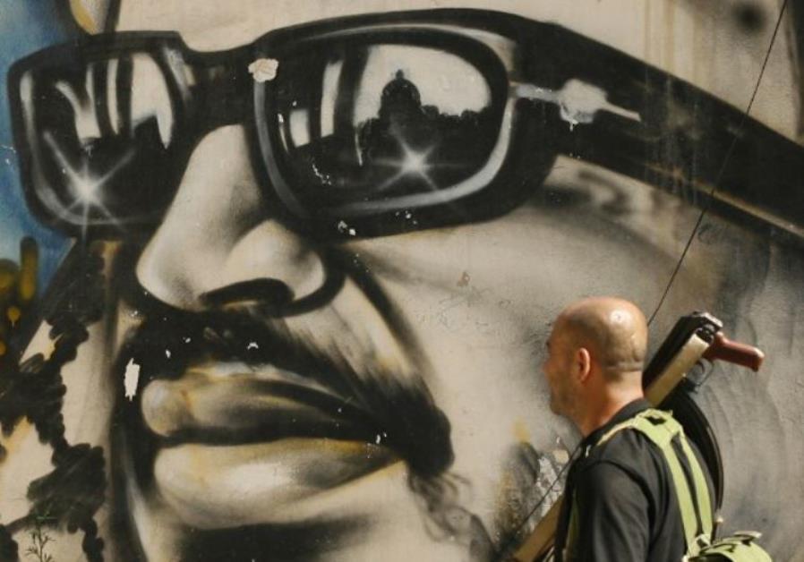 An armed man walks past a graffiti depicting late Palestinian leader Yasser Arafat in Lebanon