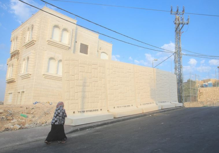A Palestinian from the east Jerusalem neighborhood of Jebl Mukaber walks past a barrier
