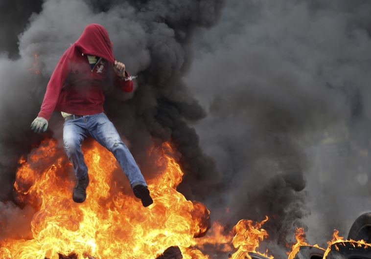 A Palestinian protester jumps over burning tires during clashes with IDF troops near Ramallah