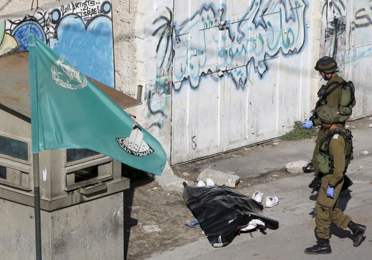 Israeli soldiers stand next to the body of a Palestinian who stabbed a soldier in Hebron
