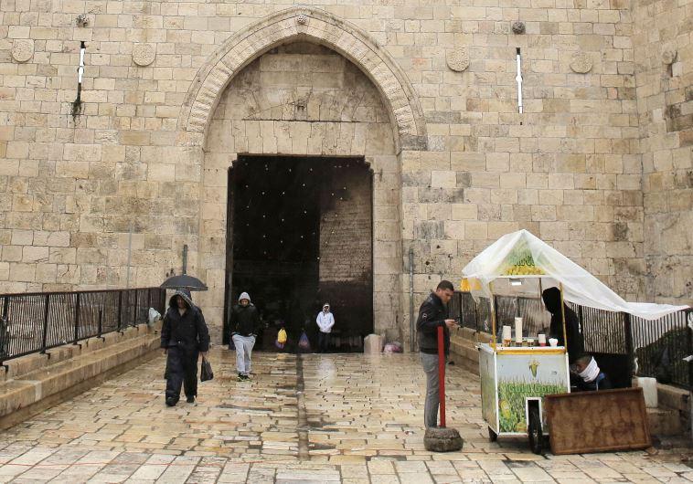 A man buys street food as it rains near Damascus Gate in Jerusalem's Old City