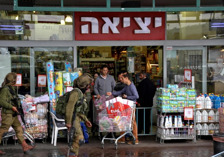 Soldiers patrolling the parking lot by the Rami Levi supermarket in the Gush Etzion commercial cente