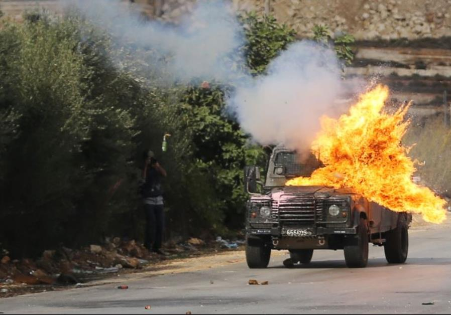A Border Police jeep is hit by a Molotov cocktail thrown by Palestinian protesters during clashes