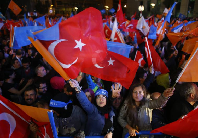 Women wave flags outside the AK Party headquarters in Ankara, Turkey
