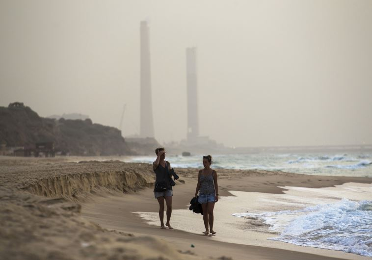 Tourists walk at the shore of the Mediterranean sea in Ashkelon in southern Israel during heavy haze