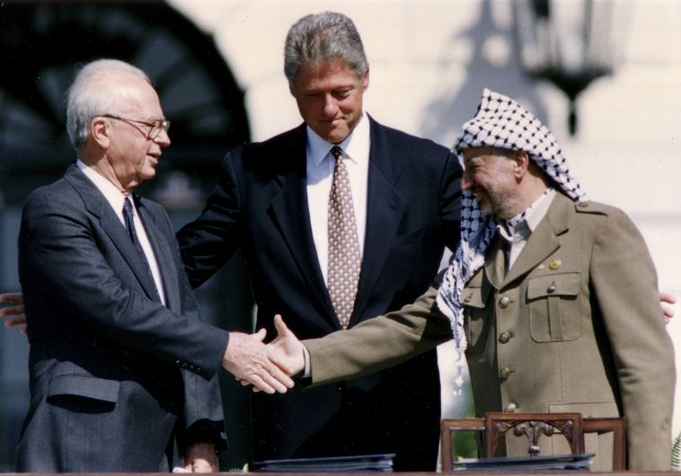 Then-PLO Chairman Yasser Arafat (R) shakes hands with then-prime minister Yitzhak Rabin (L)
