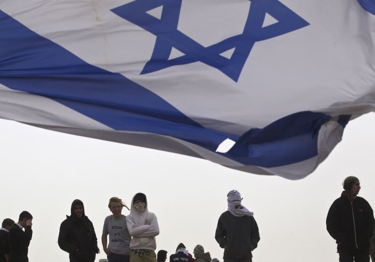An Israeli flag flutters near Israeli youths