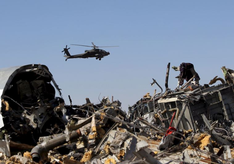 An Egyptian military helicopter flies over debris from a Russian airliner