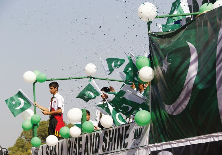 PEOPLE WAVE Pakistani flags at a rally earlier this year.