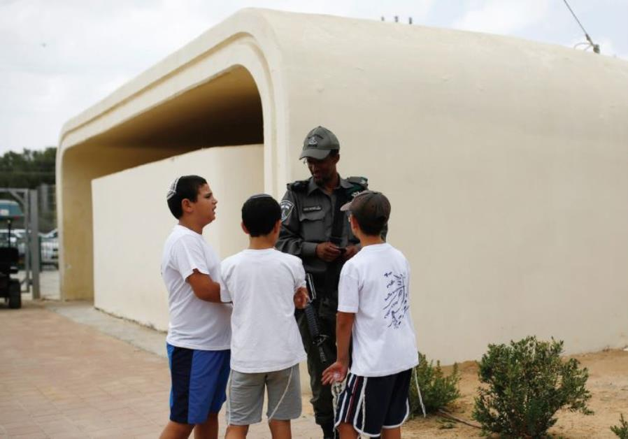 SCHOOLCHILDREN CHAT with a member of the Border Police near a bomb shelter at Kibbutz Sa'ad