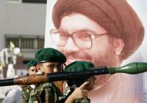 A Hezbollah member carries a mock rocket next to a poster of the group's leader, Hassan Nasrallah