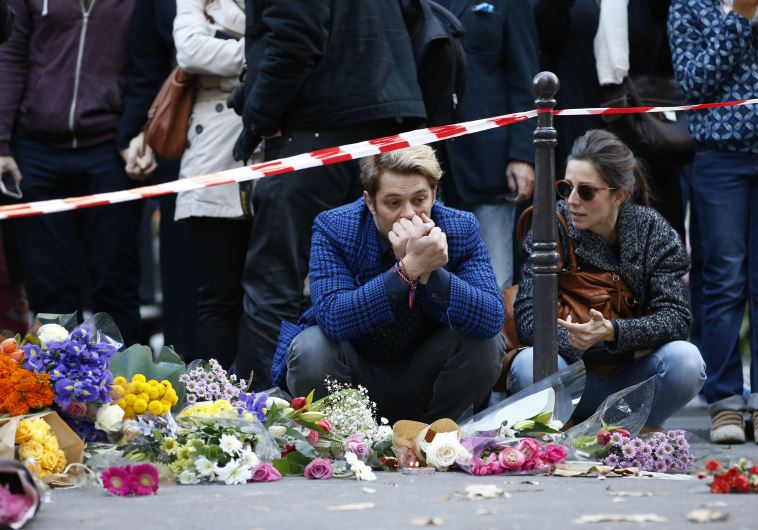 """Mourners gather at memorial sites outside of the Casa Nostra restaurant and the cafe """"Bonne biere"""" i"""