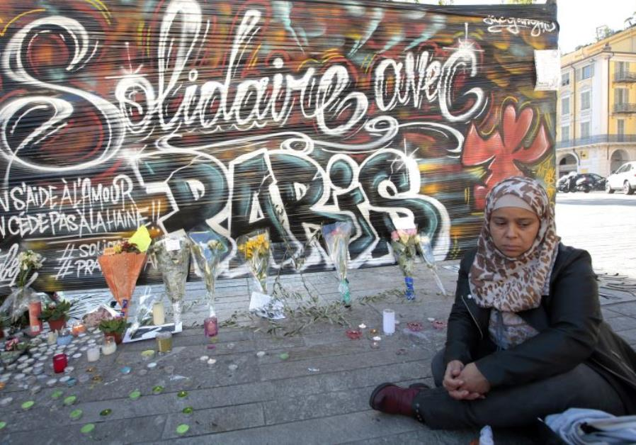 """A woman sits by a poster which reads """"Solidarity with Paris"""" in Nice, France, November 15, 2015, aft"""