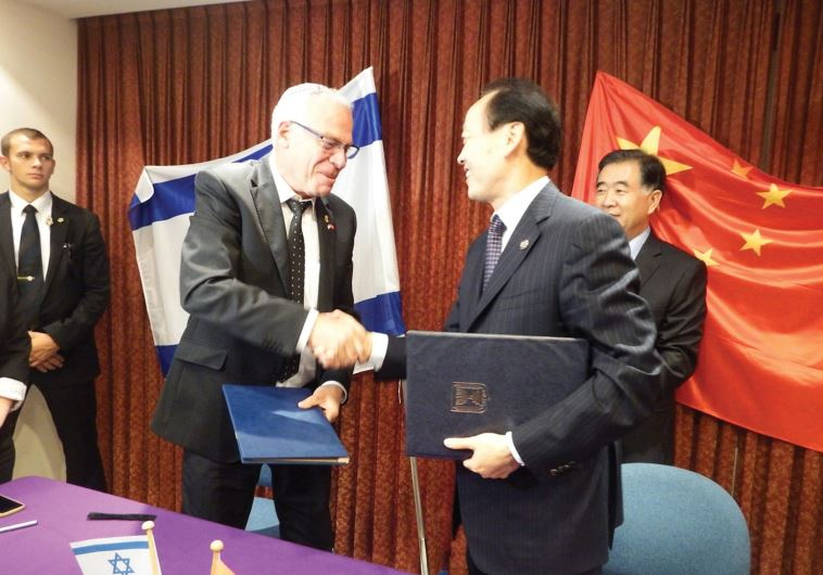 AGRICULTURE MINISTER Uri Ariel and Chinese Deputy Agriculture Minister Yu Xinrong shake hands after