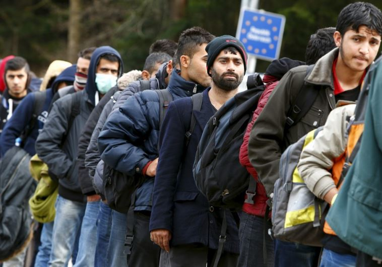 Migrants stay in a queue before passing the Austrian-German border