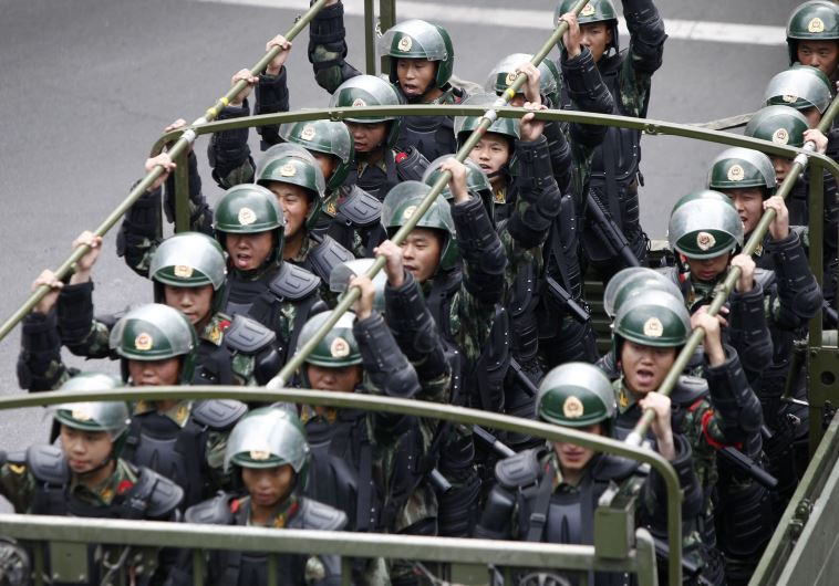Paramilitary policemen stand on a truck as they travel along a street during an anti-terrorism oath-