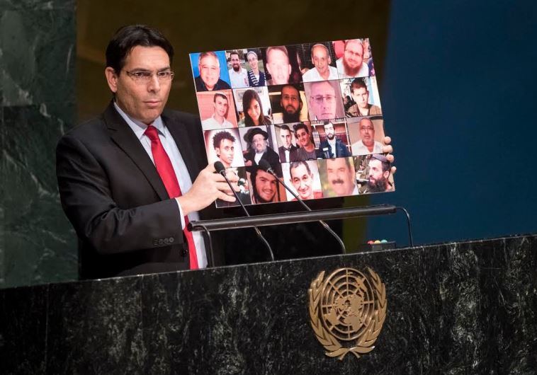 Israel's ambassador to the UN, Danny Danon, holds up a collage of terrorism victims