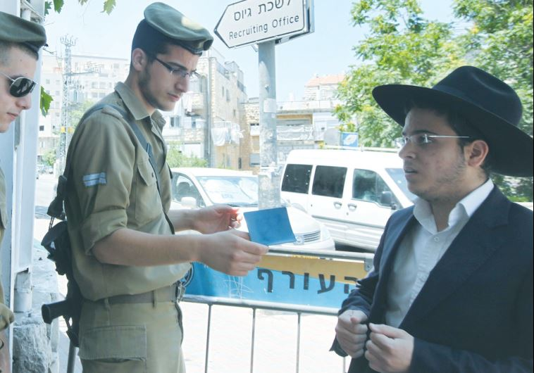 A HAREDI MAN shows his call-up notice to soldiers