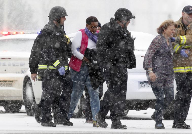 Two women are evacuated from a building where a shooter was suspected to be still holed up in Colora