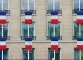 TRICOLORES HANG from Paris windows on Friday in a tribute to victims of the terrorist attacks