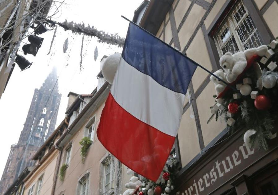 A French flag hangs from a window of a restaurant decorated for Christmas holiday season