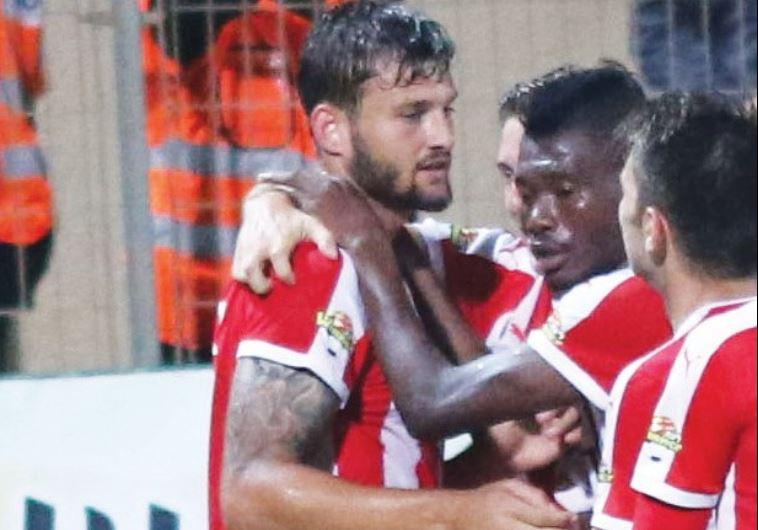 Hapoel Tel Aviv players congratulate Adi Gotlieb after he scored an 87th-minute winner