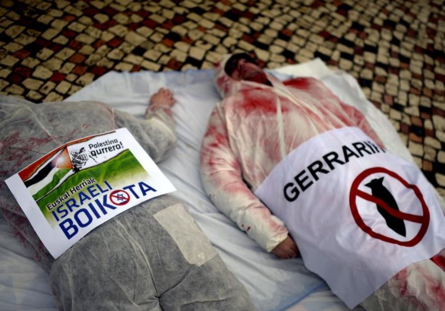 "Demonstrators lie with posters in Basque which read, ""Up With Palestinians. Boycott Israel"" (L)"