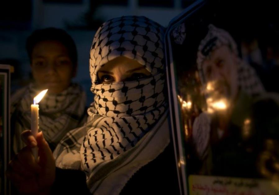 A Palestinian woman holds a candle during a protest in the southern Gaza Strip town of Khan Younis