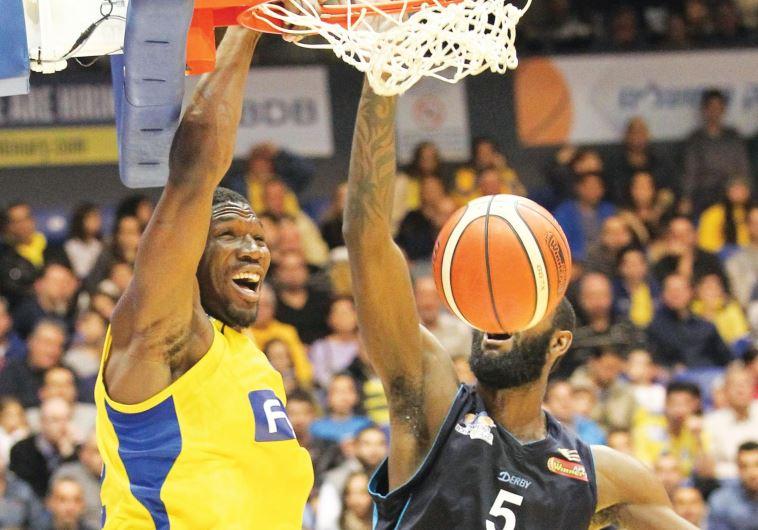 Maccabi Tel Aviv forward Trevor Mbakwe (left) dunks over Hapoel Eilat's C.J. Leslie