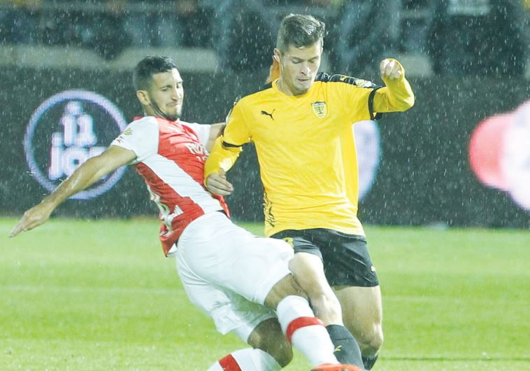 Beitar Jerusalem midfielder David Keltjens (right) and Hapoel Tel Aviv defender Ofer Verta fight for