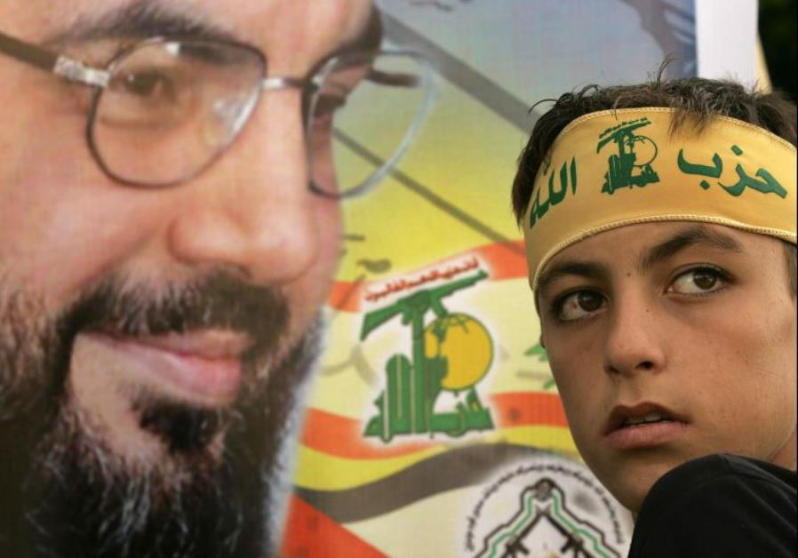 A young Hezbollah follower leans toward an image of the group's leader, Hassan Nasrallah