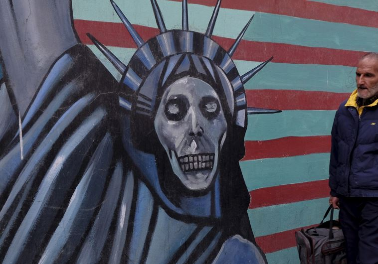 An Iranian man walks past a mural on the wall of former US embassy in Tehran