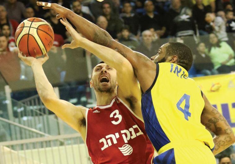 Maccabi Ashdod guard Isaiah Swann (right) blocks Hapoel Jerusalem's Tony Gaffney