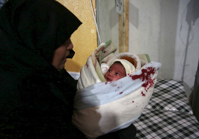 A woman carries an injured baby born inside a field hospital