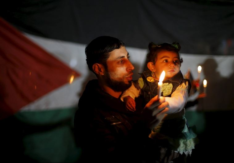 A Palestinian man and his daughter hold candles during a rally