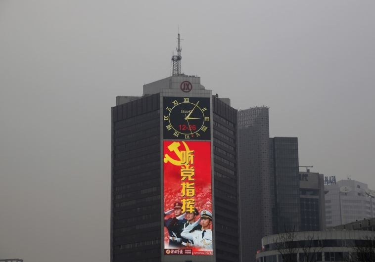 A large screen on a building shows a propaganda image of the Chinese People's Liberation Army